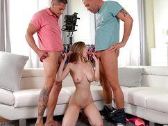 Девушка стоя на коленях старательно сосет два члена