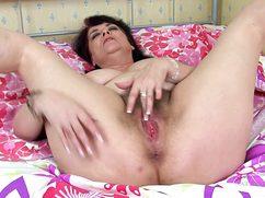 На большой кровати толстая дама дрочит киску