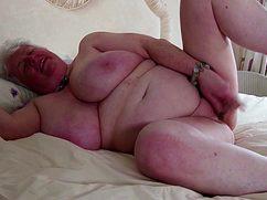 Седая и жирная бабуля выебала себя на кровати