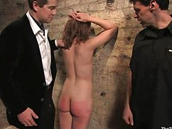 Оголенную сучку мужчины в костюмах отшлепали по жопе