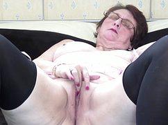 На кровати в спальне голая бабуля натирает щель