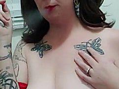 Татуированная брюнетка курит и трогает сиси перед камерой