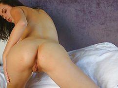 Голая симпатичная девушка на кровати принимает откровенные позы