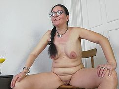Возбужденная бабка с бритой киской сидит на любимом кресле