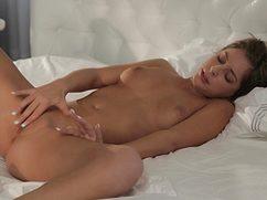 Очаровательная девушка игриво мастурбирует на постели